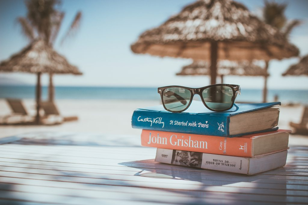 Sonnenbrillen auf Büchern am Strand